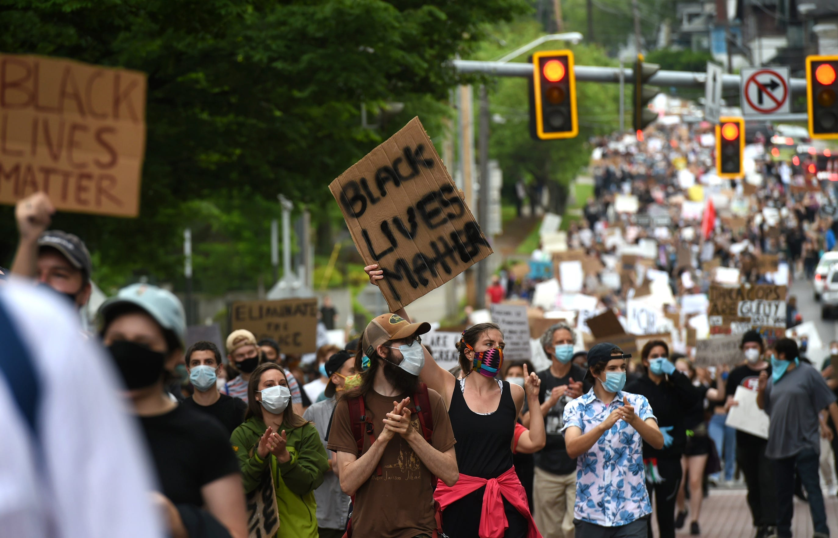 Hundreds of protesters march down a street in Ithaca, N.Y., as part of the March 4 Floyd, a peaceful protest against police brutality and systematic oppression on Wednesday, June 3, 2020.