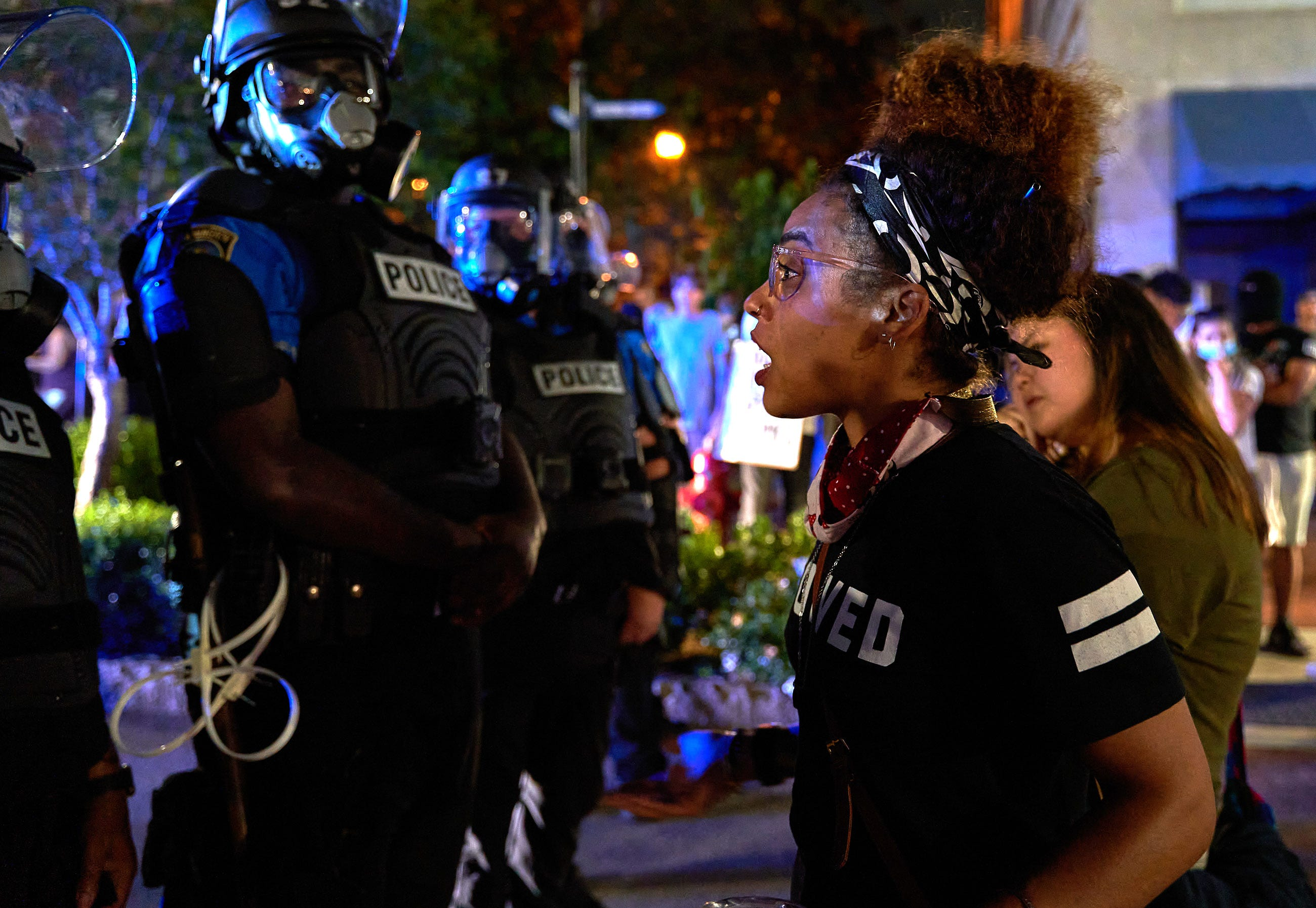 Lily Nicole talks with officers with the Wilmington Police Department during a confrontation between protesters and police in downtown Wilmington, N.C., Sunday, May 31, 2020. The protest turned confrontational as protesters and police clashed a day after a peaceful protest was held to show solidarity with George Floyd.