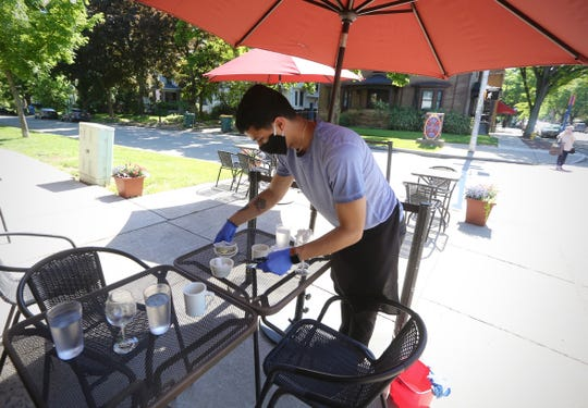 Rafael Rodriguez clears an outdoor table at Jines Restaurant, 658 Park Ave., on June 4.