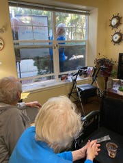 Steve Kuhn and his wife, Gwen, communicate with his parents outside their window at Prestige Senior Living Orchard Heights using a dry erase board.