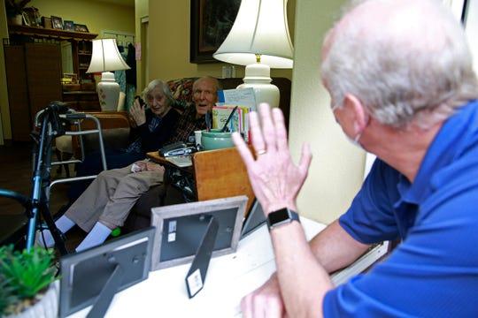 Barbara Kuhn (left) and Blaine Kuhn talk to their son Steve Kuhn through a window at Prestige Senior Living Orchard Heights in Salem, Oregon, on Wednesday, June 3, 2020.