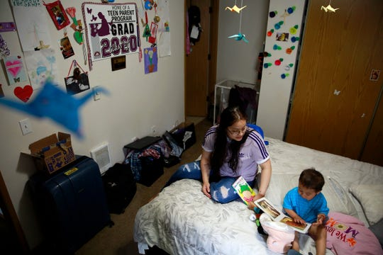 Perla Hernandez, 18, reads with her 19-month-old son Matias in her home in Salem, Oregon, on Wednesday, June 3, 2020. She is graduating from the Roberts High School Teen Parent Program this year.