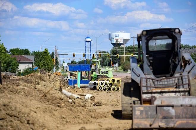 Construction workers place water mains along 85th Street on Thursday, June 4 in Sioux Falls.