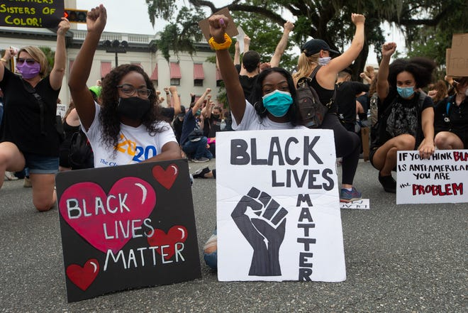 Black Lives Matter protestors marching to demand the removal of Tallahassee Police Chief Lawrence Revell and a group participating in the Justice for Humanity Walk meet in the intersection of Monroe Street and Apalachee Parkway and take a knee together Wednesday, June 3, 2020.