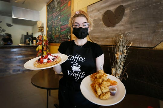 Erica Gallardo, co-owner of Coffee Waffle, shows two of the restaurant's most requested waffle options Thursday, June 4, 2020, in Clint, Texas. The most popular dishes are the chicken and waffles and the berry waffles. Coffee Waffle opened in late February.