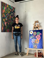 """Casas Grandes, Mexico, artist Liz """"Juppie"""" Jubizela Alvarado poses by two of her paintings Thursday, May 28, 2020, at Galeria Lincoln, 3915 Rosa Ave., in El Paso. The paintings become dazzling under a black light."""