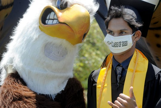 Dhruv Aggarwal  takes a photo with the Oak Park High School eagle mascot, student David Shiang, during the drive-through graduation ceremony Thursday, June 4, 2020.