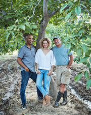Corky's Nuts founders Eric Hargrove, left, and Nicole Facciuto pose in a walnut orchard with Facciuto's father, Corky, who planted the trees in the late 1970s.