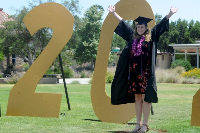 Arianna Bleau takes a photo with the 2020 sign at Oak Park High School during the drive-through graduation ceremony in June 2020. The school was named a distinguished school by the state in April.