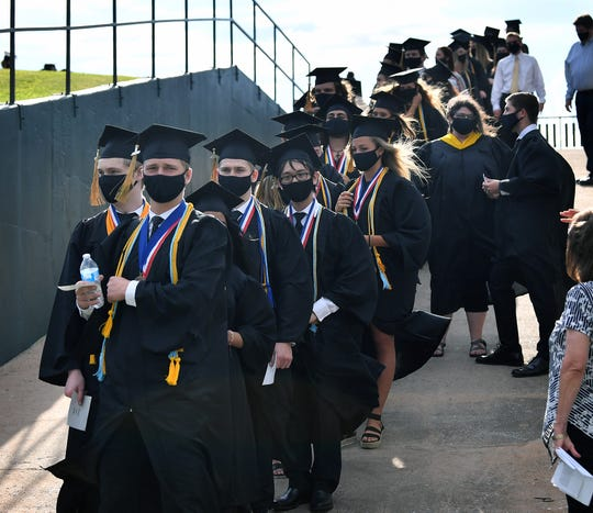 Rider High School seniors wear matching face masks as they prepare to begin commencement ceremonies at Memorial Stadium Thursday.