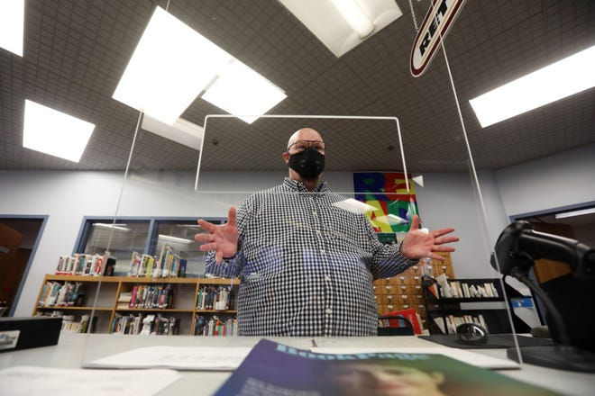 Muskingum County Library System Marketing Director Sean Fennell talks about the Plexiglas barriers at the checkout desk at the John McIntire Library.