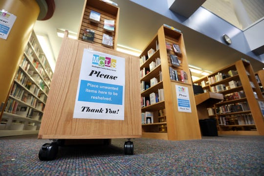 SIgns ask library patrons not to return books to the shelves of the John McIntire Library, but to place them in one of several bins around the stacks.