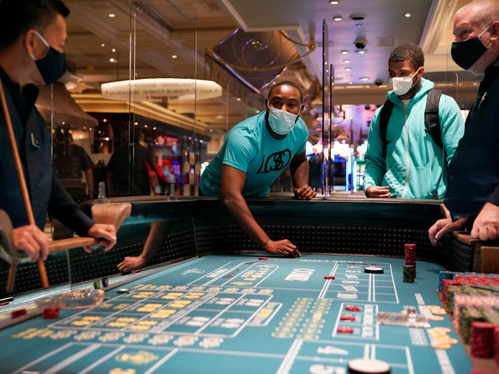 People play craps after the reopening of the Bellagio hotel and casino Thursday, June 4, 2020, in Las Vegas.