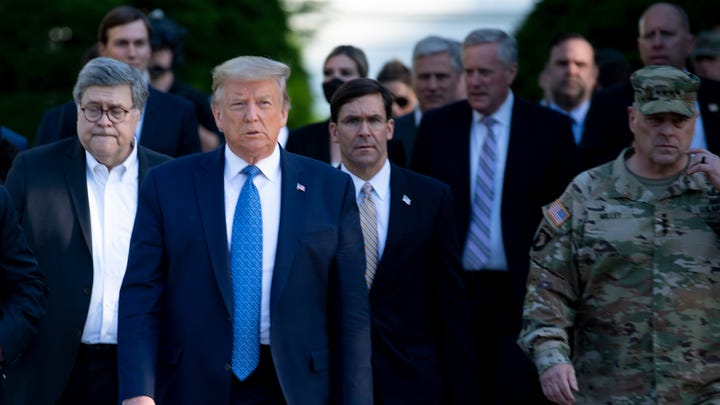 President Donald Trump walks with US Attorney General William Barr (L), US Secretary of Defense Mark T. Esper (C), Chairman of the Joint Chiefs of Staff Mark A. Milley (R), and others from the White House to visit St. John's Church after the area was cleared of people protesting the George Floyd's death.