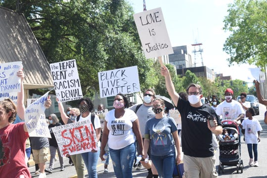 """People march on Murray Street on Friday during the Alexandria branch of the NAACP's """"Take Note"""" Rally."""