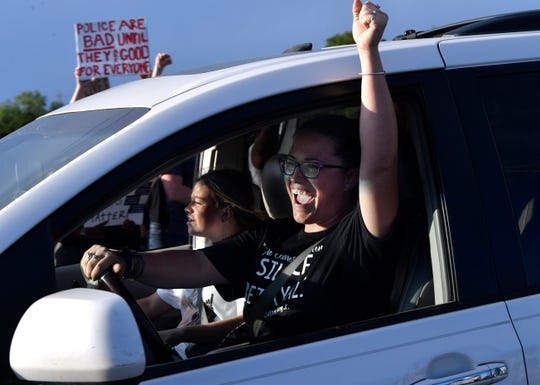 A woman raises her hand in solidarity as she passes a crowd demonstrating to remember national victims of police brutality on June 4. East Highway 80 was eventually closed as people gathered to march from the Martin Luther King Jr. Memorial Bridge sign into downtown Abilene and back.