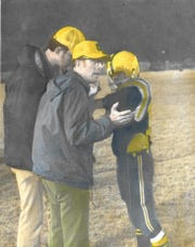 O'Brien head coach C.H. Underwood, center, talks strategy with quarterback Danny Del Hierro during a Bulldogs game. Underwood led the Bulldogs to the first six-man state football title in 1972.