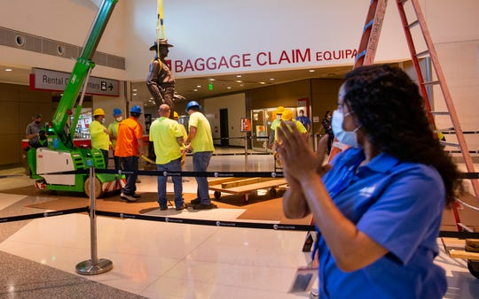 """Tiffany Anderson claps as a crew removes the Texas Ranger """"One Riot, One Ranger"""" statue by Waldine Tauch from the main lobby inside Love Field airport Thursday, June 4, 2020, in Dallas. """"He's racist, he's got to go,"""" Anderson said as she clapped. (Juan Figueroa/The Dallas Morning News via AP)"""
