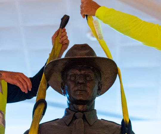 """A Phoenix 1 Restoration & Construction crew removes a 12-foot-tall bronze statue of a Texas Ranger, called """"One Riot, One Ranger,""""  from the main lobby inside Love Field airport on Thursday, June 4, 2020 in Dallas.  (Juan Figueroa/ The Dallas Morning News via AP)"""