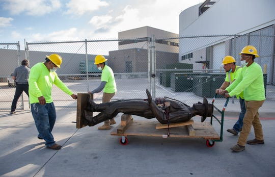 """A Phoenix 1 Restoration & Construction crew wheels a 12-foot-tall bronze statue of a Texas Ranger, called """"One Riot, One Ranger,""""  from the main lobby inside Love Field airport on Thursday, June 4, 2020 in Dallas. A published account of brutal and racist chapters in the history of an elite Texas investigative agency prompted Dallas officials to remove the statue from Love Field's passenger terminal that honored the agency. (Juan Figueroa/ The Dallas Morning News via AP)"""