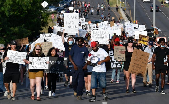 Demonstrators on June 4 march over the Martin Luther King Jr. Memorial Bridge on their way into downtown Abilene. The group, protesting nationwide police brutality, peacefully marched to Grape Street before returning.