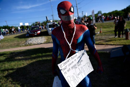 Chris Craig wore a Spider Man costume and a sign to show support for Black Lives Matter at a June 4 rally near the Martin Luther King Jr. Memorial Bridge sign on East Highway 80.