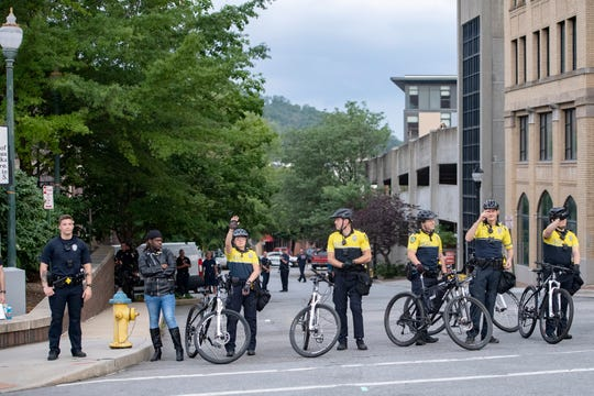 Police on bicycles stand at the Asheville Police Department as one waves as curfew nears in downtown Asheville following a vigil on June 4, 2020 in response to the May 25 death of George Floyd at the hands of Minneapolis police. Protesters abided by the emergency city curfew of 8 p.m. and left without police intervention.