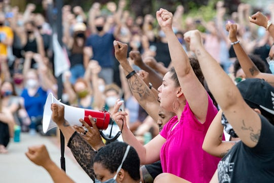 Taylor Loven addresses the crowd of about one thousand people getting them to raise their fist in solidarity as they gathered for a peaceful vigil in downtown Asheville on June 4, 2020 in response to the May 25 death of George Floyd at the hands of Minneapolis police. Protesters abided by the emergency city curfew of 8 p.m. and left without police intervention.
