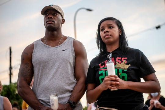 James Wimberly and Emirrora Austin attend a candlelight vigil for Ahmaud Arbery, George Floyd and Breonna Taylor on Thursday, June 4, 2020 at the Calhoun County Justice Center in Battle Creek, Mich.