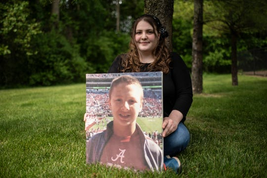 Pennfield senior Kaitlin Cook holds a portrait of her late brother Austin on Thursday, June 4, 2020 at her home in Battle Creek, Mich.