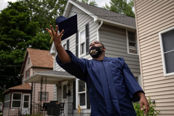 W.K. Kellogg graduate Tyberius Settles poses for portraits in his cap and gown on Thursday, June 4, 2020 at his home in Battle Creek, Mich.