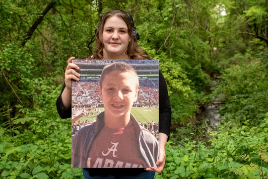 Pennfield senior Kaitlin Cook holds a portrait of her late brother Austin on Thursday, June 4, 2020 in Battle Creek, Mich.