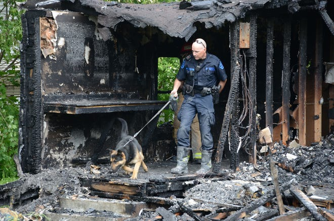 Michigan State Police Trooper Joel Service and Baki search the burned remains of a vacant house on Thursday.  Trace Christenson/The Enquirer