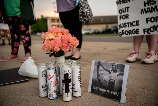 Flowers and candles are placed next to an image of Gianna Floyd, George Floyd's six-year-old daughter, on Thursday, June 4, 2020 at the Calhoun County Justice Center in Battle Creek, Mich.