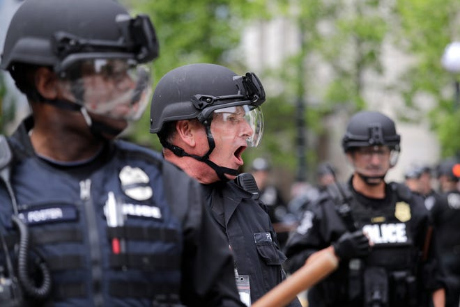 A Seattle police officer yells out orders at Seattle City Hall as protesters march toward them Wednesday, June 3, 2020, in Seattle, following protests over the death of George Floyd, a black man who died in police custody in Minneapolis.