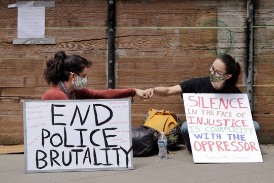 Protesters Kaylee Gore, left, and Amanda Barnes exchange fist bumps as they sit with signs protesting police actions, Thursday, June 4, 2020, in Seattle, following protests over the death of George Floyd in Minneapolis. Seattle's police chief says officers' badge numbers will be prominently displayed following complaints that black bands obscured the digits.