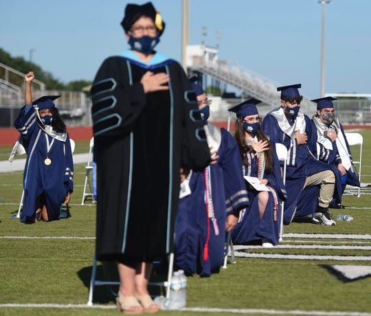 A Collegiate High School senior raises a fist as others kneel for the national anthem at their 2020 graduation.