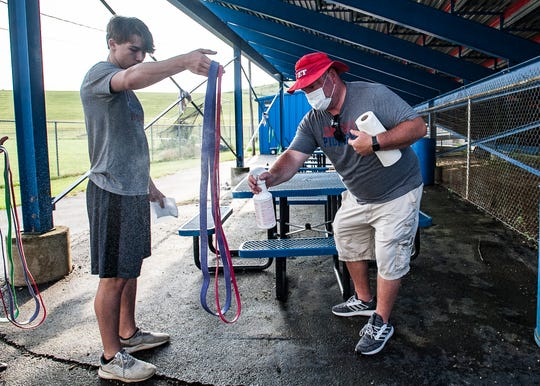 Zane Trace assistant coach Chris Shanton sprays down elastic bands used by Kaleb Frankopoulos so they can be disinfected and wiped down for usage by the next group of football players. Modified football practices began this week as schools adapt to changes caused by the coronavirus epidemic.