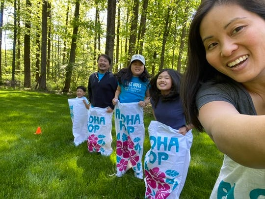 The Kang family. Mia, Sydney, and Trey, participate in sack races with their parents.