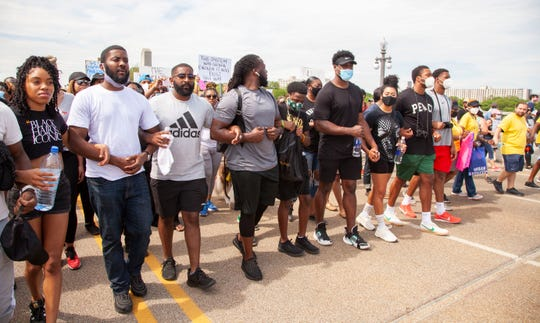 Former Detroit Lions player, Joique Bell, center leads protesters arm and arm as they march across the MacArthur Bridge across the Detroit River to and from Belle Isle during a rally in Detroit, Friday, June 5, 2020, protesting police brutality and the death of George Floyd.