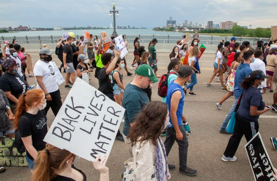 Protesters march on the MacArthur Bridge across the Detroit River to and from Belle Isle during a rally in Detroit, Friday, June 5, 2020, protesting police brutality and the death of George Floyd.