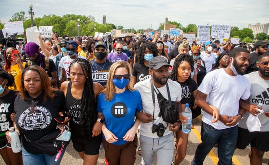 Secretary of State Jocelyn Benson, third from the left, leads protesters arm and arm as they march across the MacArthur Bridge across the Detroit River to and from Belle Isle during a rally in Detroit, Friday, June 5, 2020, protesting police brutality and the death of George Floyd.