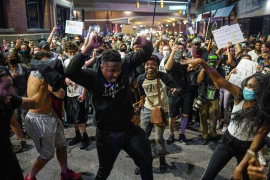 Protesters dance while marching back towards Detroit Police Department after being successful in having the curfew called discretionary as they march through downtown Detroit on the sixth day of protests against police brutality on Wednesday, June 3, 2020.