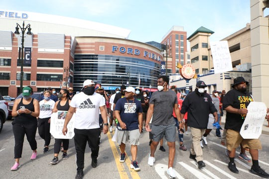 High school football coaches from across the Detroit metro area walk together for a peace march in Downtown Detroit on Thursday, June 4, 2020.