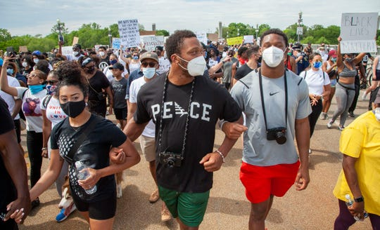 Detroit Lions player, Romeo Okwara, center, and his brother Julian, right, lead protesters arm and arm as they march across the MacArthur Bridge across the Detroit River to and from Belle Isle during a rally in Detroit, Friday, June 5, 2020, protesting police brutality and the death of George Floyd.