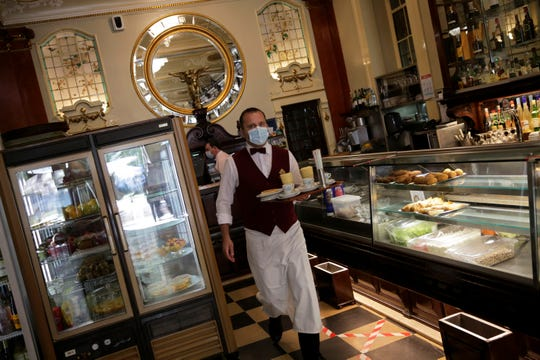 A waiter wearing a face mask carries a tray at the Versailles restaurant and pastry shop in Lisbon, Monday, May 18.