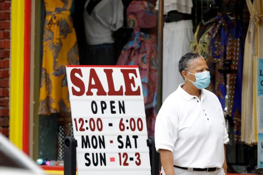 A woman walks past a boutique with a sale sign, Thursday in Cleveland Heights, Ohio.