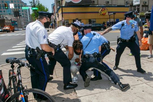 Philadelphia police tackle a man after he attacked Associated Press Photographer Matt Rourke on Thursday, June 4, 2020.
