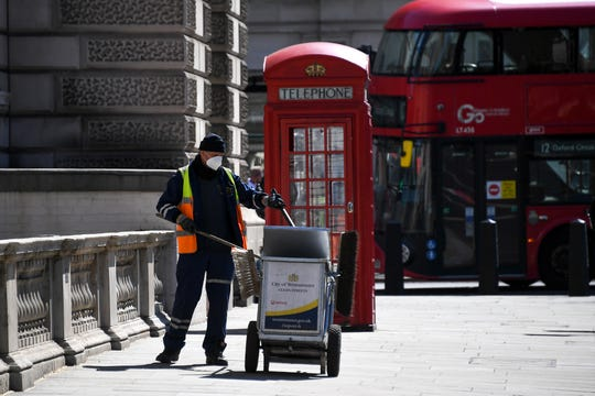 A council worker wearing a face mask to protect against coronavirus, collects refuse at Parliament Square, in London, Monday, May 18.