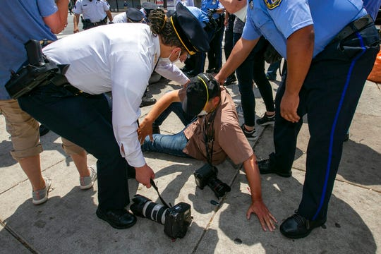 Police Commissioner Danielle Outlaw, left, and other officers attend to Associated Press photographer Matt Rourke after he was assaulted while touring the business district with Philadelphia Mayor Jim Kenney and police officers in Philadelphia on Thursday, June 4, 2020.